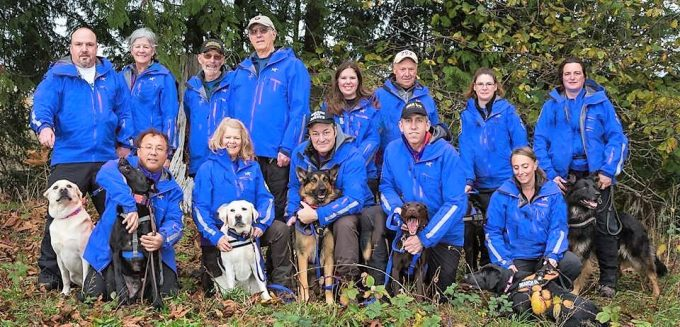 A group of people in blue jackets with their dogs