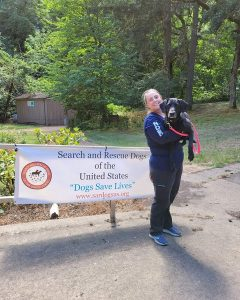 Woman standing in front of a sign holding a dog