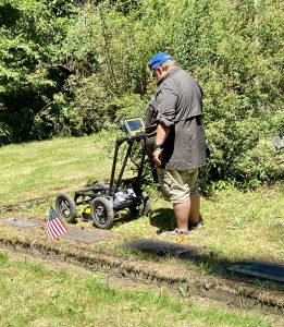 Man using a ground penetrating radar system on a gravesite